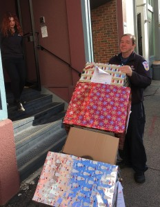 Armstrong Support Services Ed Kelly delivering boxes of winter boots and socks upstairs to Bay Cove Human Services dressing room.