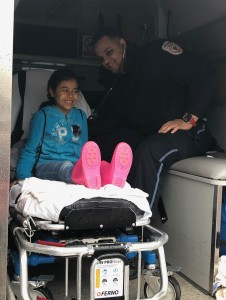 Armstrong EMT Remy Cortorreal checks a child's heart and lungs during the touch-a-truck portion of an Easter egg hunt in Brighton.
